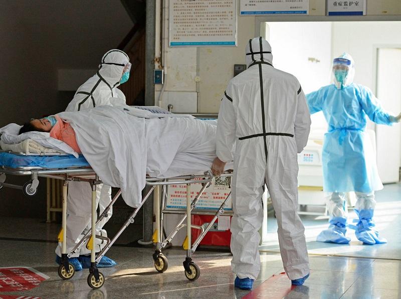 Pessoa em maca e médicos completamente protegidos