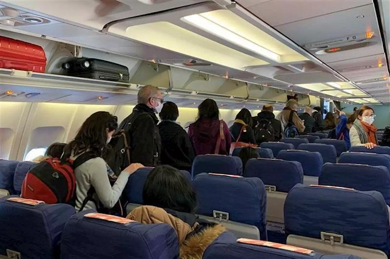 Pessoas com máscara dentro de avião